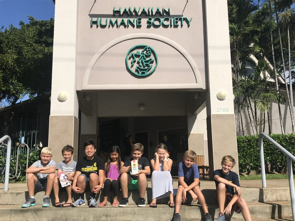 Children representing Brutus Broth sit in front of the Hawaiian Humane Society, where they chose to donate proceeds